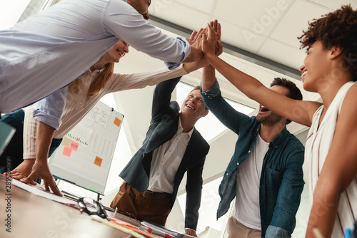 Obraz We did it Business people giving each other high-five and smiling while working together in the modern office - fototapety do salonu