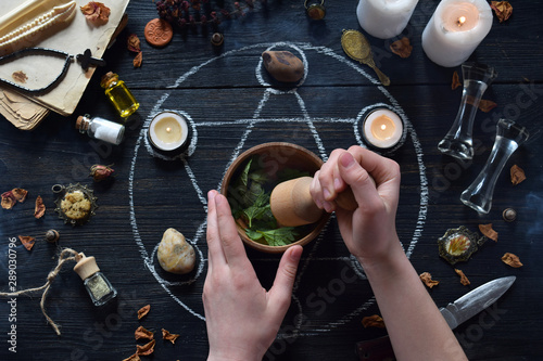Fotografie, Obraz Womens hands make love potion on pentagram circle with candles, stones and old books on witch table