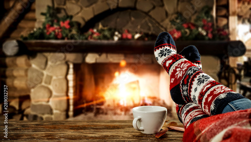 Woman legs with christmas socks and fireplace  - 289032757
