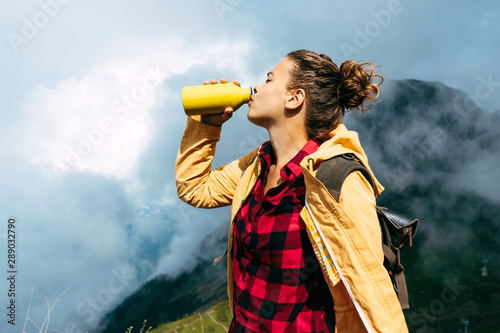 A young caucasian woman in the mountains in a yellow waterproof jacket and with a backpack stands and drinks water from a personal refillable bottle Tapéta, Fotótapéta