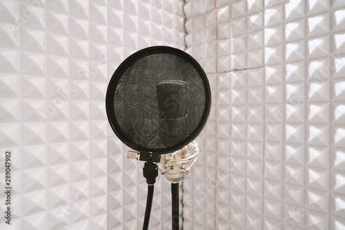 Valokuvatapetti microphone with pop filter on mic stand in soundproof isolation booth for vocal