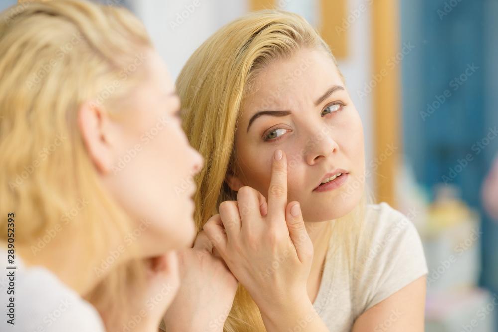 Fototapeta Woman looking at her skin in mirror