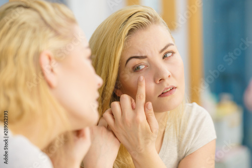 Woman looking at her skin in mirror