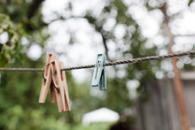 Colorful Plastic Clothespins On The Hangers With Blurred Background