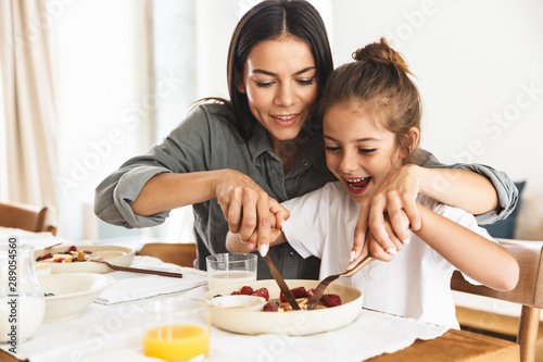 Fototapeta Image of amazing family mother and little daughter eating together while having breakfast at home in morning obraz