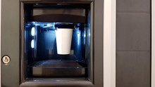 White Paper Cup In The Window Of A Vending Coffee Machine. The Process Of Making Coffee In A Wading Machine