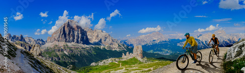 Cycling woman and man riding on bikes in Dolomites mountains andscape Wallpaper Mural