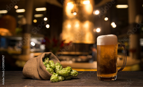 Biere, Cidre Beer brewing ingredients Hop in bag and wheat ears on wooden cracked old table. Beer brewery concept. Hop cones and wheat closeup. Sack of hops and sheaf of wheat on vintage background.