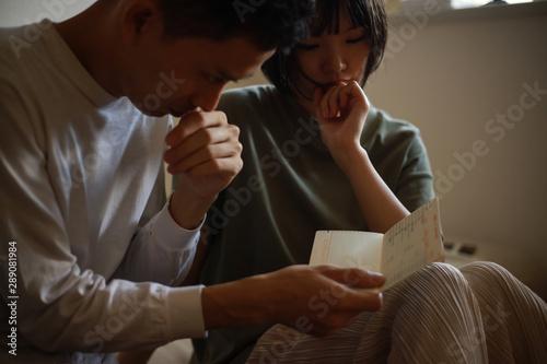 通帳を見ながら悩む夫婦 Fotobehang