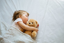 Little Baby Sleeping On Bed At Home With Soft Toy. Free Space