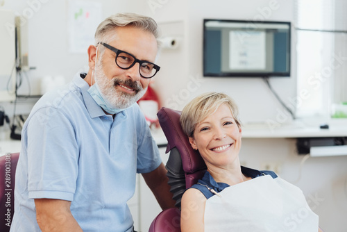 Smiling dentist with a happy woman patient