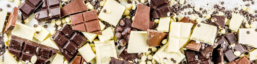 Fototapety, obrazy: Assorted different types of chocolate. Broken pieces of dark, milk and white chocolate, with nuts, cooking chocolate, shavings. top view copy space