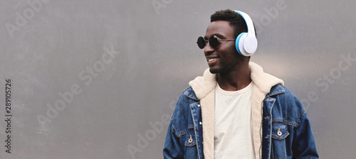 Photo sur Aluminium Magasin de musique Portrait happy smiling african man in wireless headphones listening to music looking away at blank copy space gray metal wall background