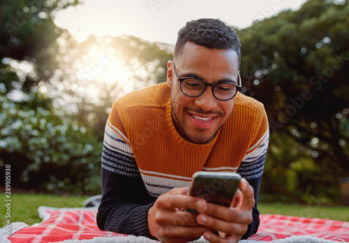 Poster Attraction parc Portrait of an african smiling young man student wearing black eyeglasses relaxing in park using smart phone - college student using mobile in park