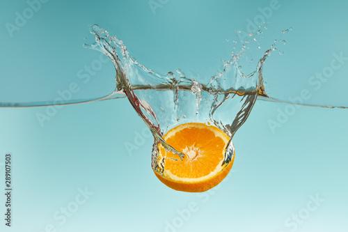 Fototapeta owoce w wodzie   swiezy-pomaranczowy-pol-wchodzacych-w-wode-z-pluskiem-na-niebieskim-tle