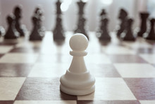 Single Pawn Against Many Enemies As A Symbol Of Difficult Unequal Fight Or Struggle Of Minorities. Background In Blur.
