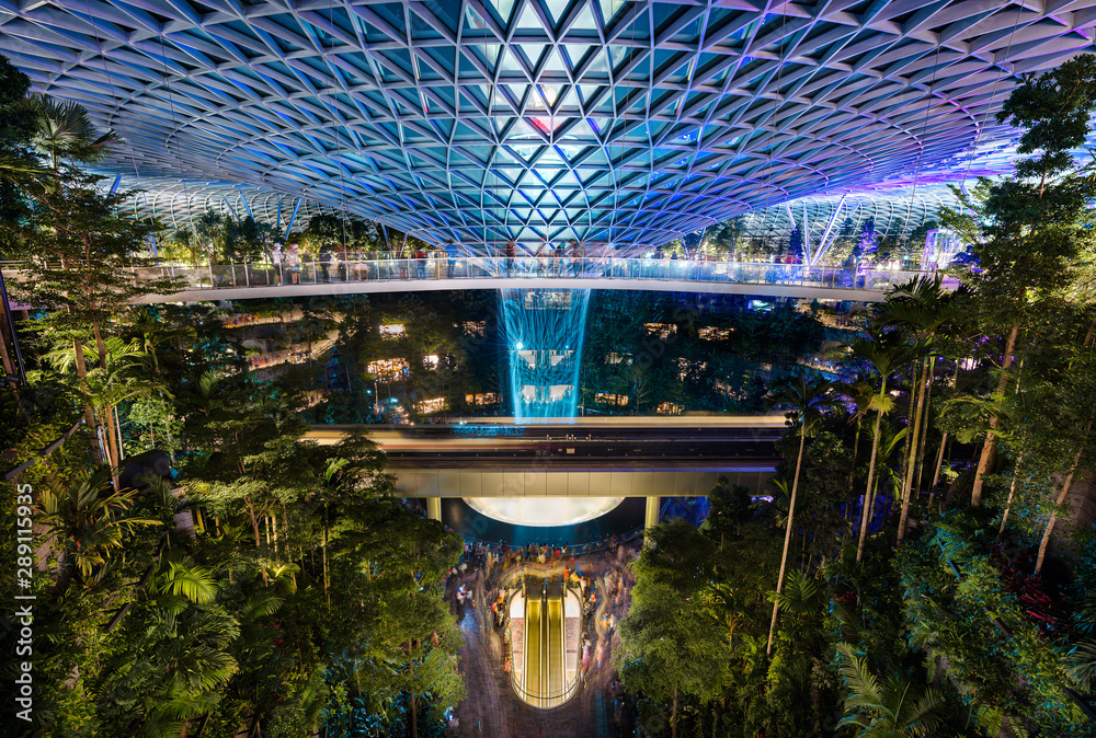 Fototapeta The Jewel at Changi Airport, with the rain vortex indoor waterfall illuminated during the light show, Singapore