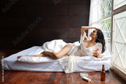 Vászonkép drunken asian woman in white lingerie, drinking glass of liquor alcohol and smok