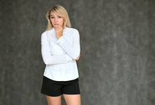 Portrait Of A Pretty Blonde Manager Girl In A White Blouse On A Gray Background. Right In Front Of The Camera In Various Poses.