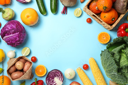Different vegetables and fruits on blue background, copy space