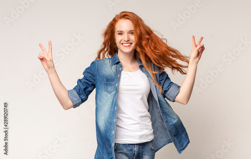 Cadres-photo bureau Pain Cheerful teen girl smiling and demonstrating v-sign over light background