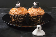 Happy Halloween Orange And Black Decorated Cupcake With A Black Witch Hat And Butter Cream With Beads On A Black Plate.