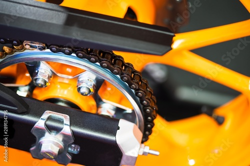 Photo  Chain and gear wheel of new yellow motocycle close up