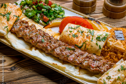 lula kebab spicy with vegetables in Turkish on the board Canvas Print