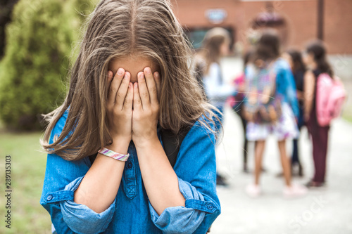 Fotomural A sad Teenage girl outside the school with student on the back