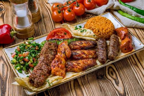 assorted kebabs with bulgur and vegetables Turkish cuisine on wooden table Canvas Print
