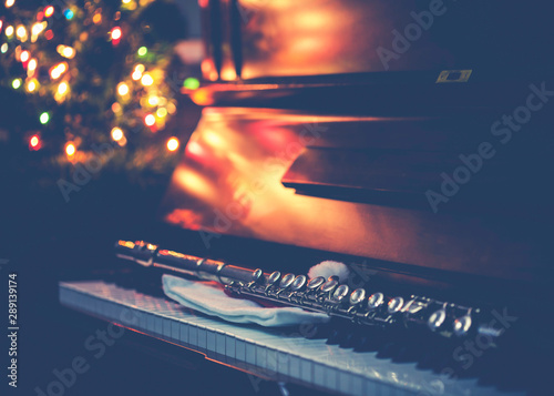 close up of clarinet on piano keys against Christmas decoration light, Christmas background - 289139174
