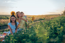 Outdoor Photo Of Beautiful Smiling Family, Teen Girl In Striped Blue Dress Sitting On Plaid Among The Mealow With Sunflower On Her Head, Her Brother Hugging His Happy Young Mom In Yellow Shirt