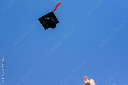 black graduate hat with red tassel flies to the blue sky tossed hand girl studen Fototapet