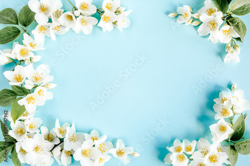 Frame of jasmine flowers, petals, leaves on blue background Canvas Print