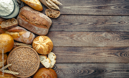 Foto op Canvas Brood Assortment of baked bread on wooden table background,top view