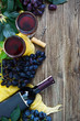 Wineglasses with red wine, bottle, corkscrew, blue grapes, leaves on a wooden table. Wine background with copy space. Top view, flat lay