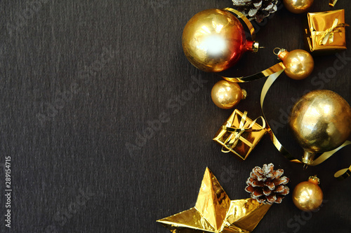 Fototapeta Merry Christmas and Happy New Year. Flat lay photo with gold gift boxes and decorations on black background. Xmas greeting card, banner. Copy space for the text obraz na płótnie