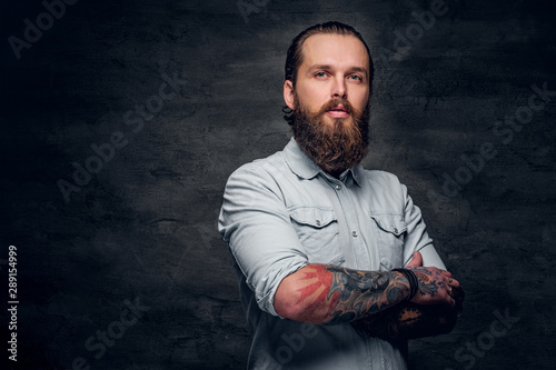 Groomed bearded man with tattooes is posing at dark photo studio. Fototapet
