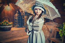 Portrait Of A Beautiful Girl In A Vintage Dress With An Umbrella. Retro Picture. Art Style