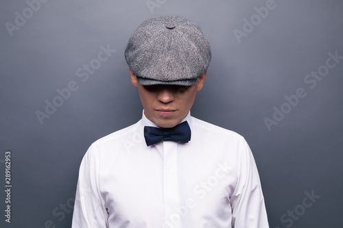 Photo Mysterious portrait of retro 1920s english gangster with flat cap