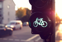 Close Up On Traffic Light For A Cycling Lane Showing Green Bicycle Symbol In Bright Toned Morning Light - Blurred Background With Cars - Urban Commuting Concept