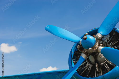 Fototapeta Close up abstract of a vintage airplane propeller engine against blue sky, closeup