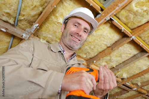 Obraz low angle view of mature builder holding cordless drill - fototapety do salonu