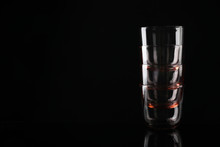 Stack Of Empty Colorful Whiskey Glasses On Black Background, Space For Text
