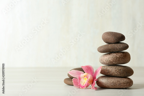 Stack of spa stones and flower on table against white background, space for text Canvas Print