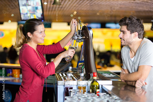 barmaid serving a pint to customer in a bar Wallpaper Mural
