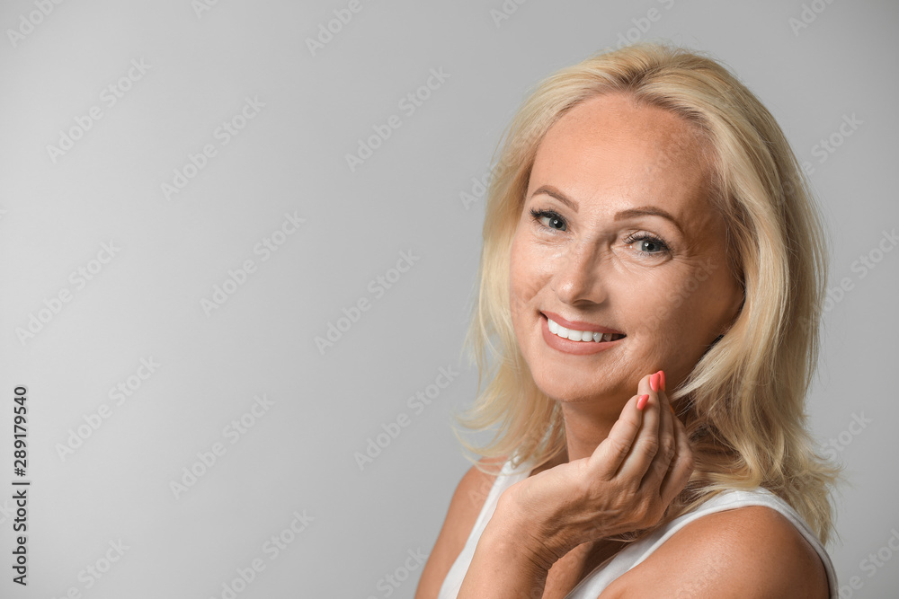 Fototapeta Portrait of beautiful mature woman with perfect skin on grey background. Space for text