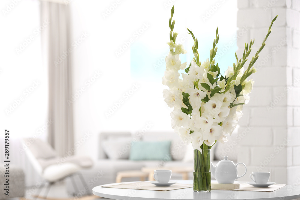 Fototapeta Vase with beautiful white gladiolus flowers on wooden table in living room. Space for text