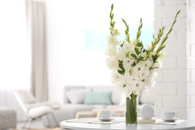 Vase With Beautiful White Gladiolus Flowers On Wooden Table In Living Room. Space For Text