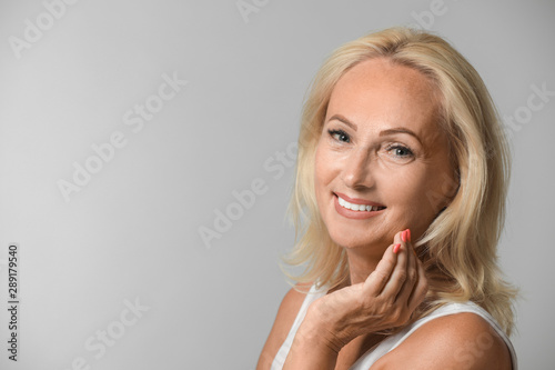 Portrait of beautiful mature woman with perfect skin on grey background Wallpaper Mural